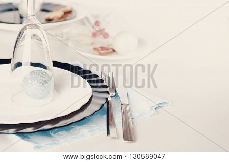 Stylish blue and silver Christmas table setting on white and black dinnerware with New Year with a blue ball under the glass .Toned photo