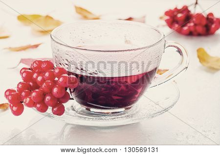 Red berries of viburnum and cup of tea  on white bacgraund .Toned photo