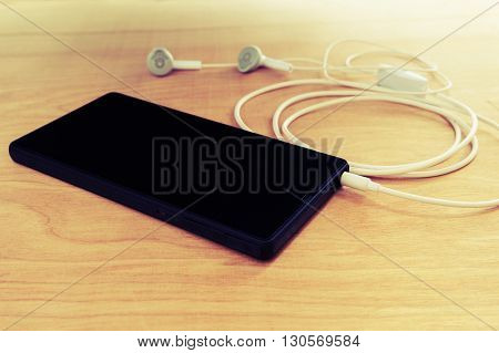 Emotion of relax Smart phone black screen with earphone on wooden table Vintage style