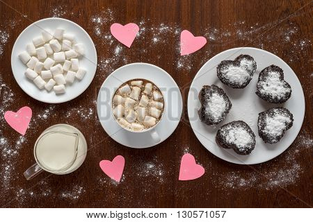 Paper hearts on a coffee table on wooden background.There are also a cup of coffee, a plate with cup cakes, a saucer with marsh mallow and a glass jar with milk.