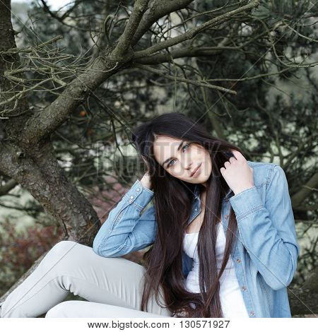 Pretty girl posing in the park on the background of fir trees