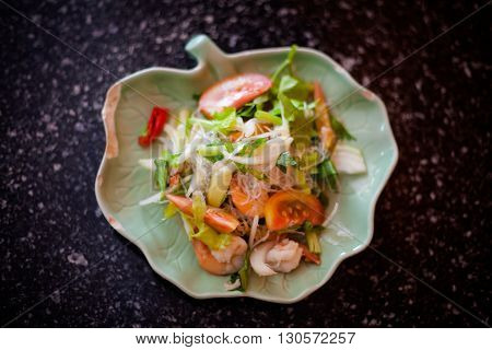 Fresh made hot seafood salad with glass noodle tomatoes cilantro and onion. Traditional thai cuisine.