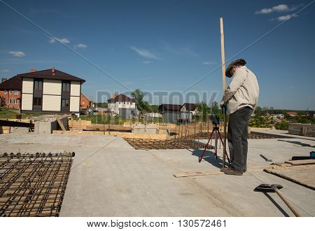 Men is mesuring height level of the building foundation with special equipment