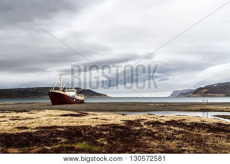 abandoned fishing boat on the deserted north-western fjords of Iceland on an overcast rainy day