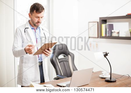 Doctor Reading A Patient's History In An Office
