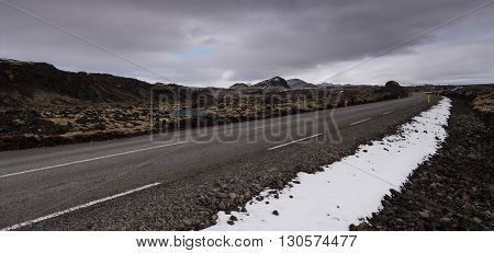 Rural empty straight road in Reykjanes peninsula in Iceland with direction to the snowing mountains