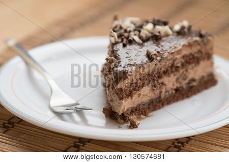 Slice of fresh delicious chocolate cake on a plate garnished with nuts and a small fork.