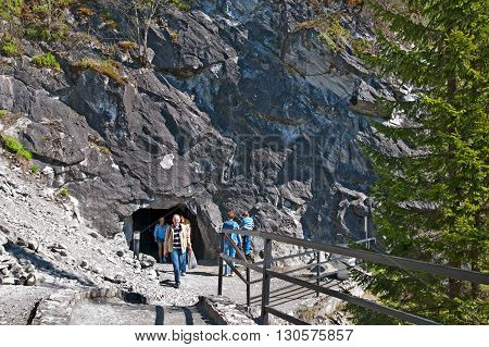 RUSKEALA, KARELIA, RUSSIA - MAY 14, 2016: People go out from the old tunnel in The Mountain Park