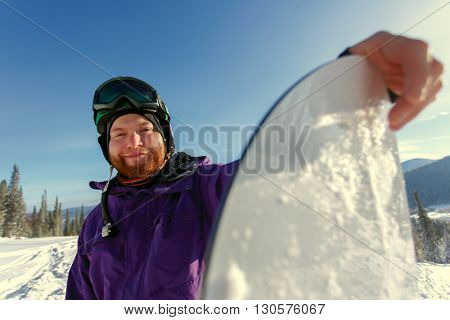 Snowboarder holds snowboard on top of hill, close up portrait