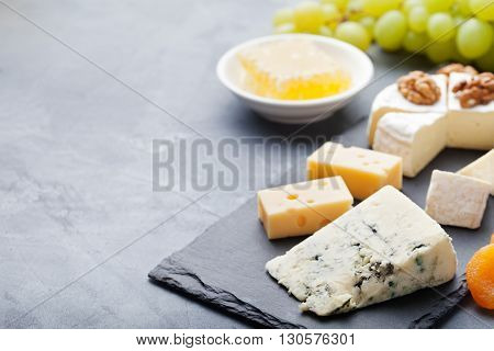 Glass of white wine and assorted cheese with grape on a stone and slate background