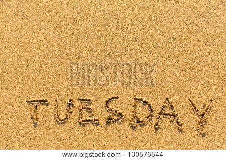 Tuesday - inscription by hand on a light-golden beach sand.