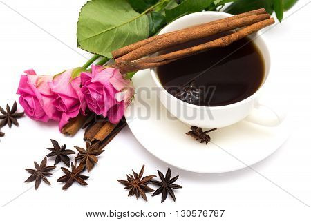 Cup of coffee with cinnamon and anise and a bouquet of pink roses