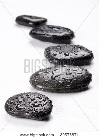 spa basalt stones and green leaves with water drops
