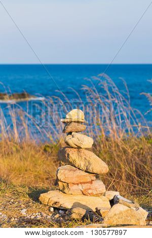 Stack of stones on beach with blue skyline background