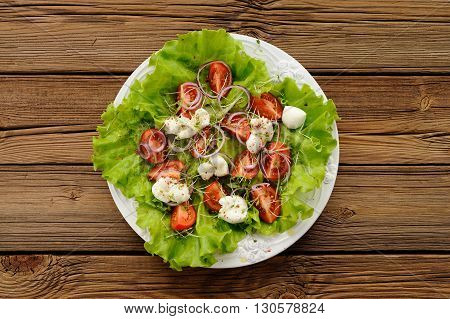Fresh salad with tomatoes lettuce mozarella and watercress on old wooden table overhead view