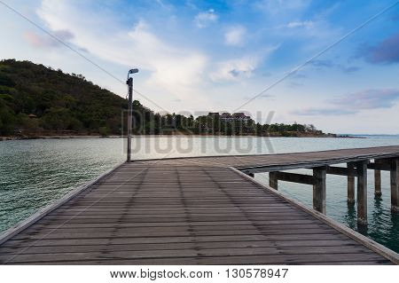 Wooden bridge leading to the sea with mountain background, natural landscape