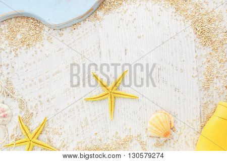Sea travel frame. Sea shells, fishing net and  suntan loton on a wooden background, Top view, vintage toned image, blank space