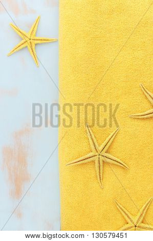 Summer vacation background. Concept of the summer time with starfish and beach towel on the wooden rustic blue background