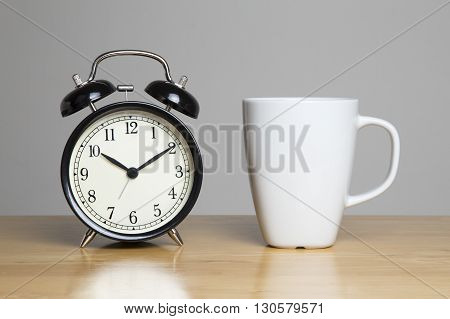 Cup of tea and alarm clock on unit