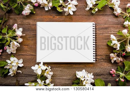 White paper mock up on rustic wood background with natural style decorations spring white blossom. Blank template, art letters, background space for text. Natural border background vintage mock up.
