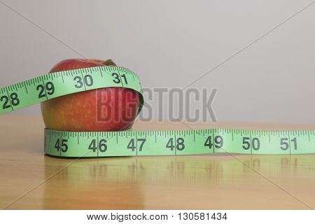 Apple and a measuring tape weight concept