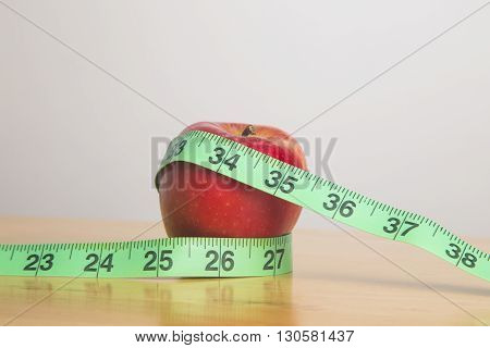 Green measuring tape around an apple on a desk