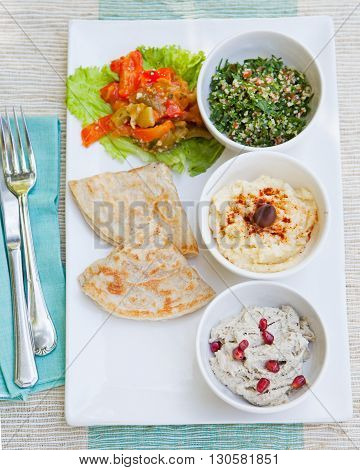 Assortment of dips: hummus, chickpea dip, tabbouleh salad, baba ganoush and flat bread, pita on a plate. Summer outdoor background Top view Copy space