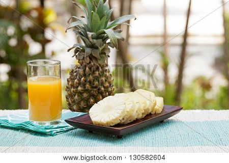 Glass of pineapple smoothie, juice and fresh fruit on a outdoor tropical background
