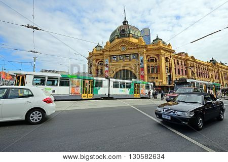 MELBOURNE, AUSTRALIA - OCTOBER 24, 2015: Vehicles buses and cars passing by the Flinders Street Station. The station is the major interchange for suburban trains in Melbourne.