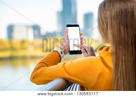 Woman in yellow sweater holding phone with white screen on the modern city background.