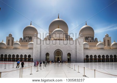 ABU DHABI, UNITED ARAB EMIRATES - APRIL 17, 2014. Visitors at Sheikh Zayed Grand White Mosque in Abu Dhabi, United Arab Emirates.
