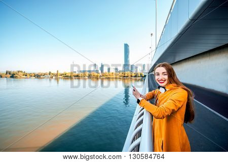 Young sport woman in yellow sweater photographing with smart phone standing on the modern bridge with skyscrapers on the background. Wide angle image with copy space
