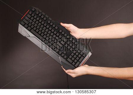 Teenage boy with computer keyboard isolated on black background
