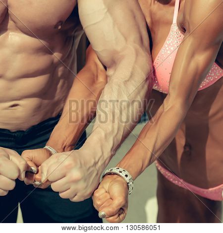 Sporty couple man and woman bodybuilders show strong arms with visible veins fists muscular physique in gym on blurred background
