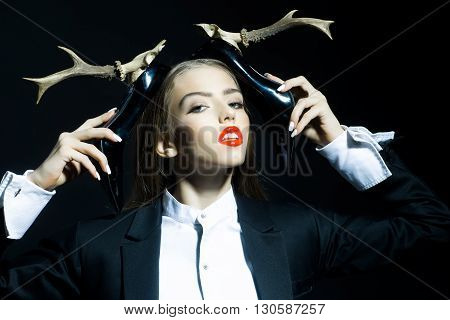 Glamour young lady with pretty face and red lips holding black patent leather shoes with high heels of animal antlers in jacket and shirt