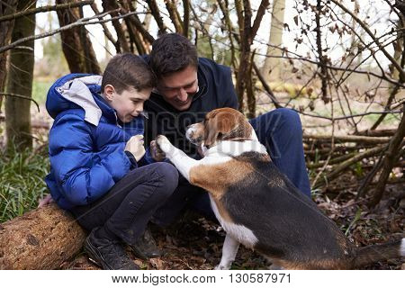 Father and son playing with dog under a shelter of branches