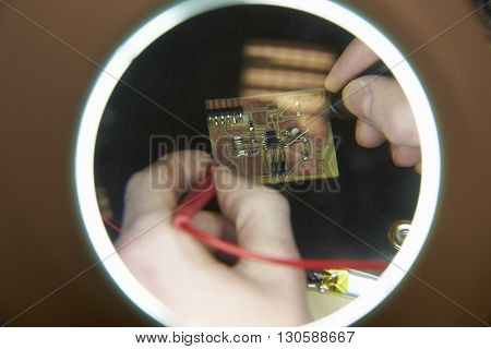 Close Up Of Electrical Engineer Soldering Circuit Board