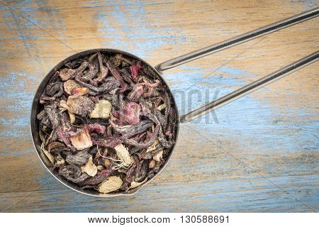 measuring scoop of a blood circulation and metabolism herbal tea including hibiscus and ginger