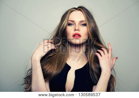 Beautiful young and emotional woman model posing at studio in the light flashes.