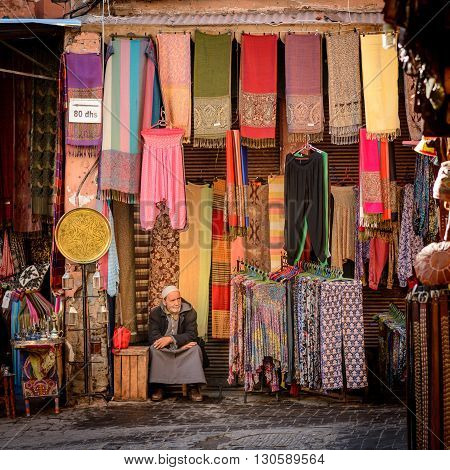 MARRAKECH MOROCCO - NOVEMBER 04 2015: A man sitting at his fabric shop in the souk of Marrakech in Morocco.
