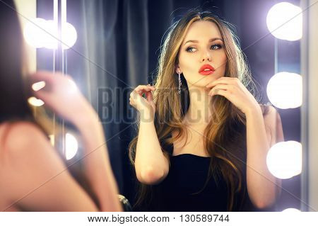 Beautiful sexy young caucasian woman looking into makeup mirror at herself and enjoying her time.