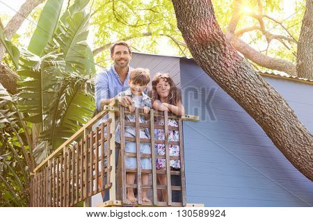Family enjoying their vacation on a tree house. Son and daughter standing on the balcony of a tree house with their father. Cheerful family relaxing at tree house.
