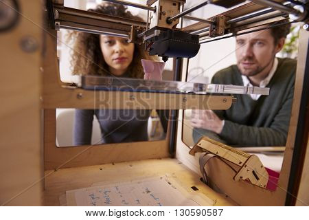 Two Designers Working With 3D Printer In Design Studio