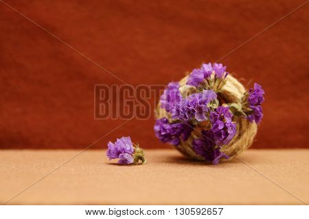 Decorative composition of twine and purple flowers on a brown background