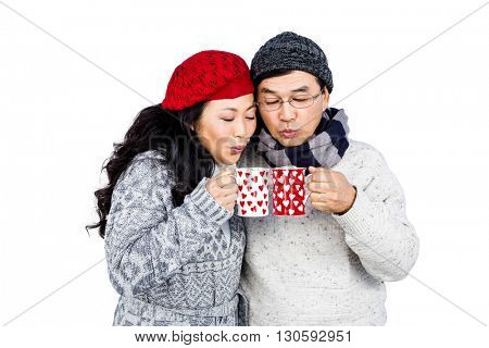 Happy couple blowing on cups against white background