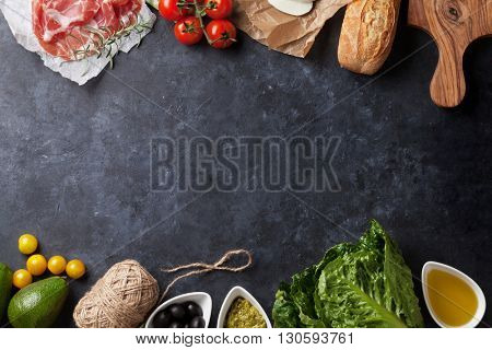 Ciabatta sandwich cooking with romaine salad, prosciutto and mozzarella cheese over stone background. Top view with copy space