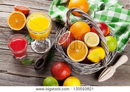 Fresh ripe citruses and juice. Lemons, limes and oranges on wooden background