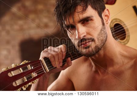 Closeup photo of handsome young man holding guitar on shoulder, looking at camera, bare chest.