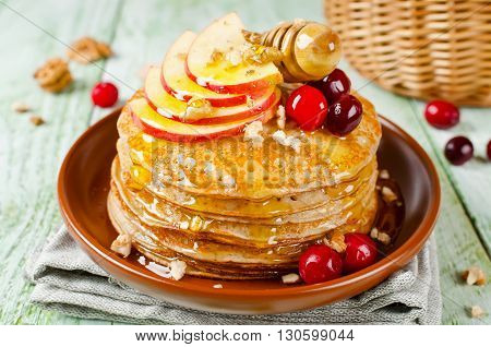 Homemade pancakes with honey apple cranberries and nuts. A stack of pancakes on a wooden table