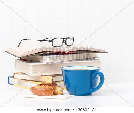 Fresh coffee and a donut in front of a small stack of textbooks.
